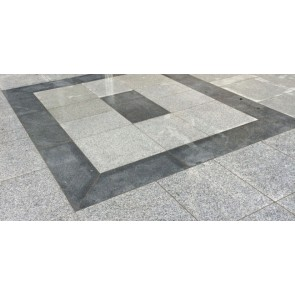 Dark grey granite paving slabs used as a boarder